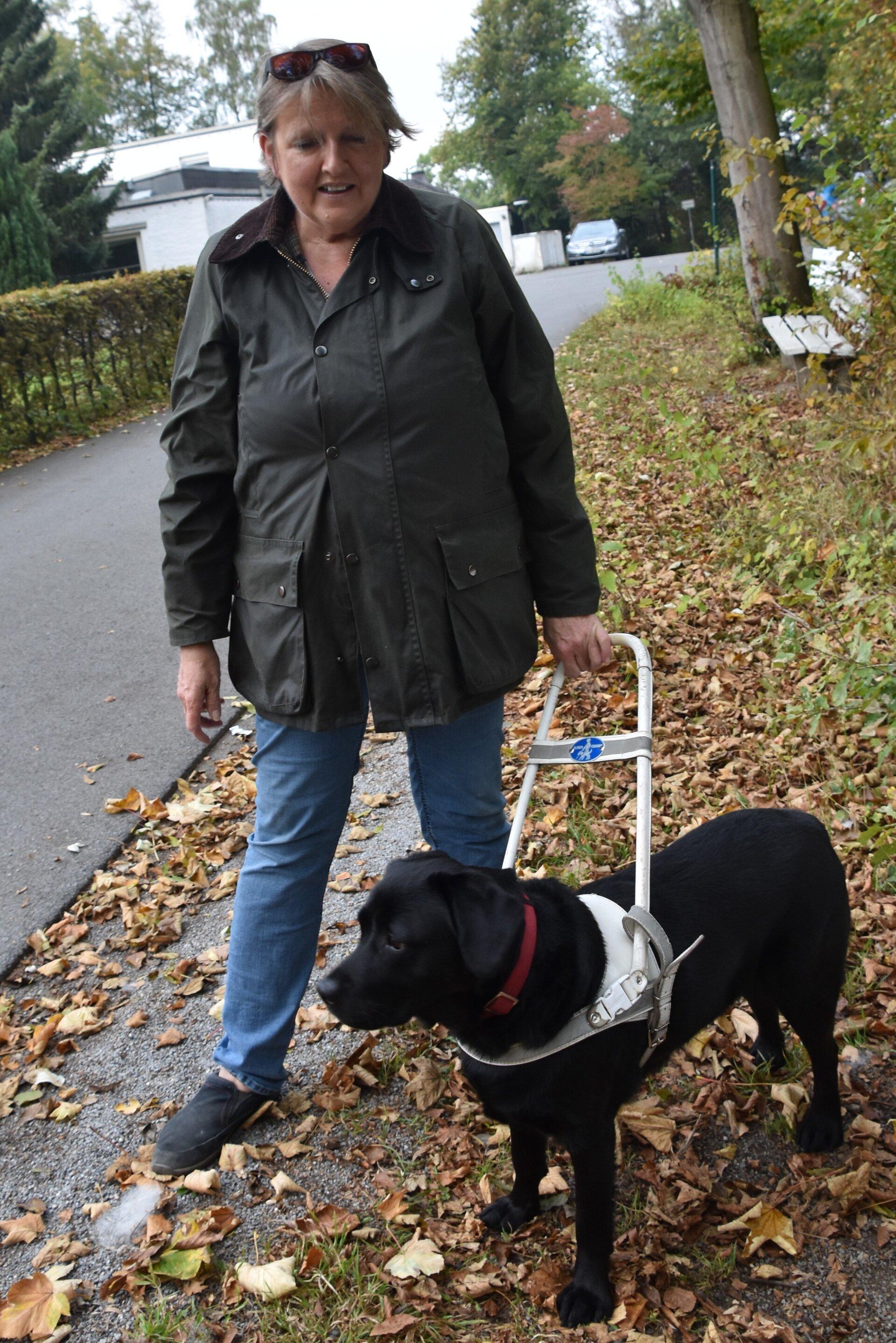 Andrea mit schwarzem Labrador Emmi im Führgeschirr