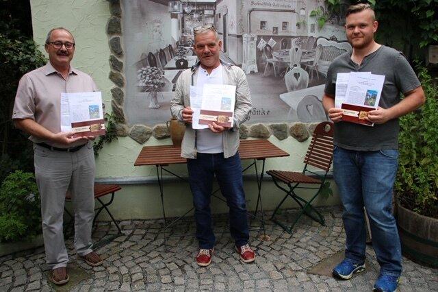 Bürgmeister und Wirtsleute präsentieren die Gewinner-Gutscheine