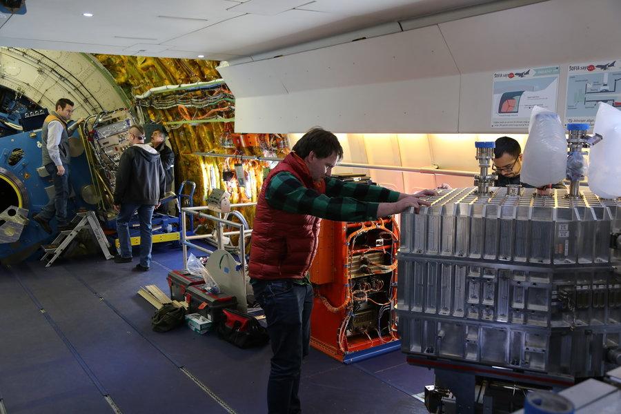 DSI-Mitarbeiter bugsieren FIFI-LS durch die enge Flugzeugtür