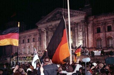At midnight on the night of October 2 to 3, 1990, the flag of unity was raised on a large flagpole in front of the Reichstag building in Berlin marking the German Unification.. Source: Bundesarchiv, Bild 183-1990-1003-400 / Grimm, Peer / CC-BY-SA 3.0; https://de.wikipedia.org/wiki/Tag_der_Deutschen_Einheit#/media/Datei:Bundesarchiv_Bild_183-1990-1003-400,_Berlin,_deutsche_Vereinigung,_vor_dem_Reichstag.jpg