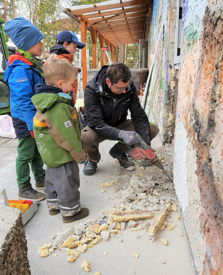 Kinder schauen dem Handwerker zu
