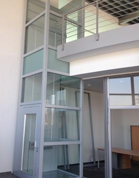 Rollstuhllifter Mia im Stahl-Glas-Schacht in einem Bürogebäude