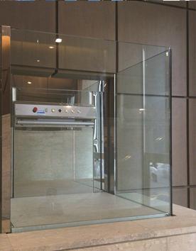 Rollstuhllifter mit eleganten Glaswänden im Innenbereich eines Museums