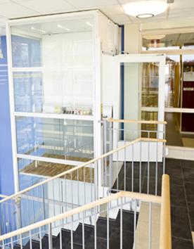 Senkrechtlift A7000 mit Stahl-Glas-Schacht in einem Konzerngebäude