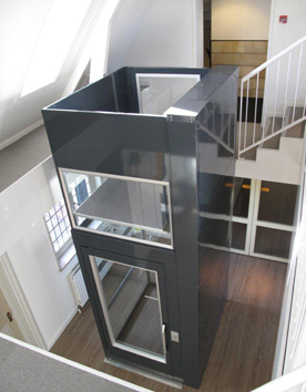 Senkrechtlift A7000 freistehend im Stahl-Glas-Schacht in einem Pultdachhaus