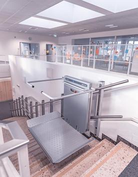 Rollstuhlhebebühne PLK 8 an einer Podesttreppe im Büroggebäude installiert