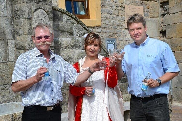 Bürgermeister Á. Nemes, Brunnenköniginn Caroline und Amtsleiter J. Höhne stellen das neue Tafelwasser vor