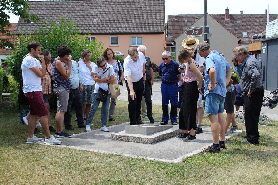Pfr. Reese erläutert den Teilnehmenden den Gedenkstein in Mönchsroth