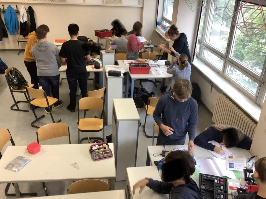 Aktive Schüler*innen bei einem Versuch.