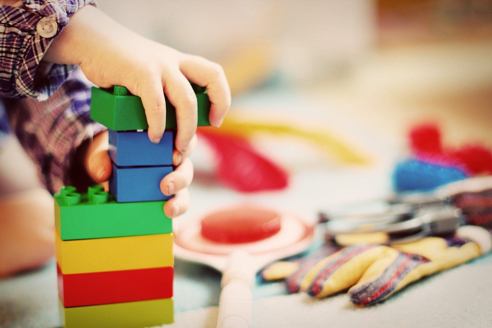 Ein Kind baut einen Turm aus Duplosteinen