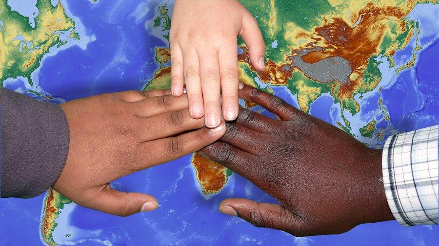 Bild zeigt Hände von Menschen verschiedener Hautfarbe auf einer Weltkarte, Foto: pixabay