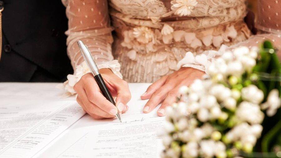 Eine Braut unterschreibt im Familienbuch