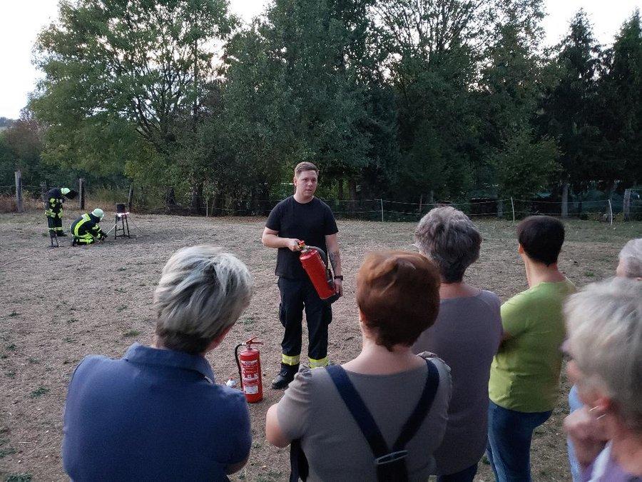 Unser Wehrführer (Julien Dahler) erklärt die Nutzung verschiedener Feuerlöschermodelle den ortsansässigen Frauen.