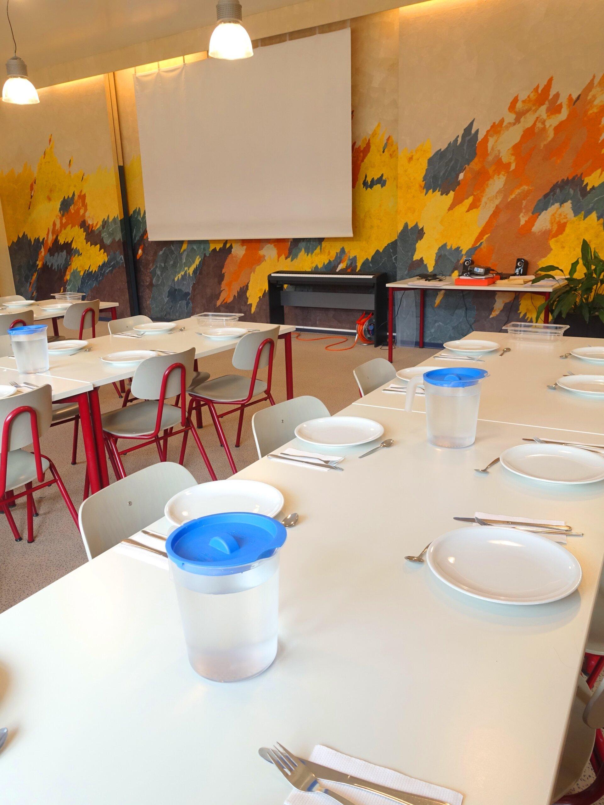 Tische und Leinwand im Speisesaal