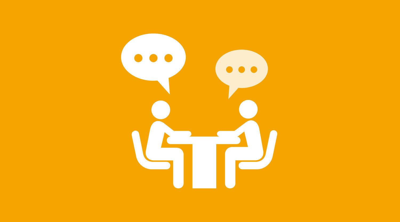 Piktogramm Beratung: Zwei Personen sitzen an einem Tisch und sprechen miteinander