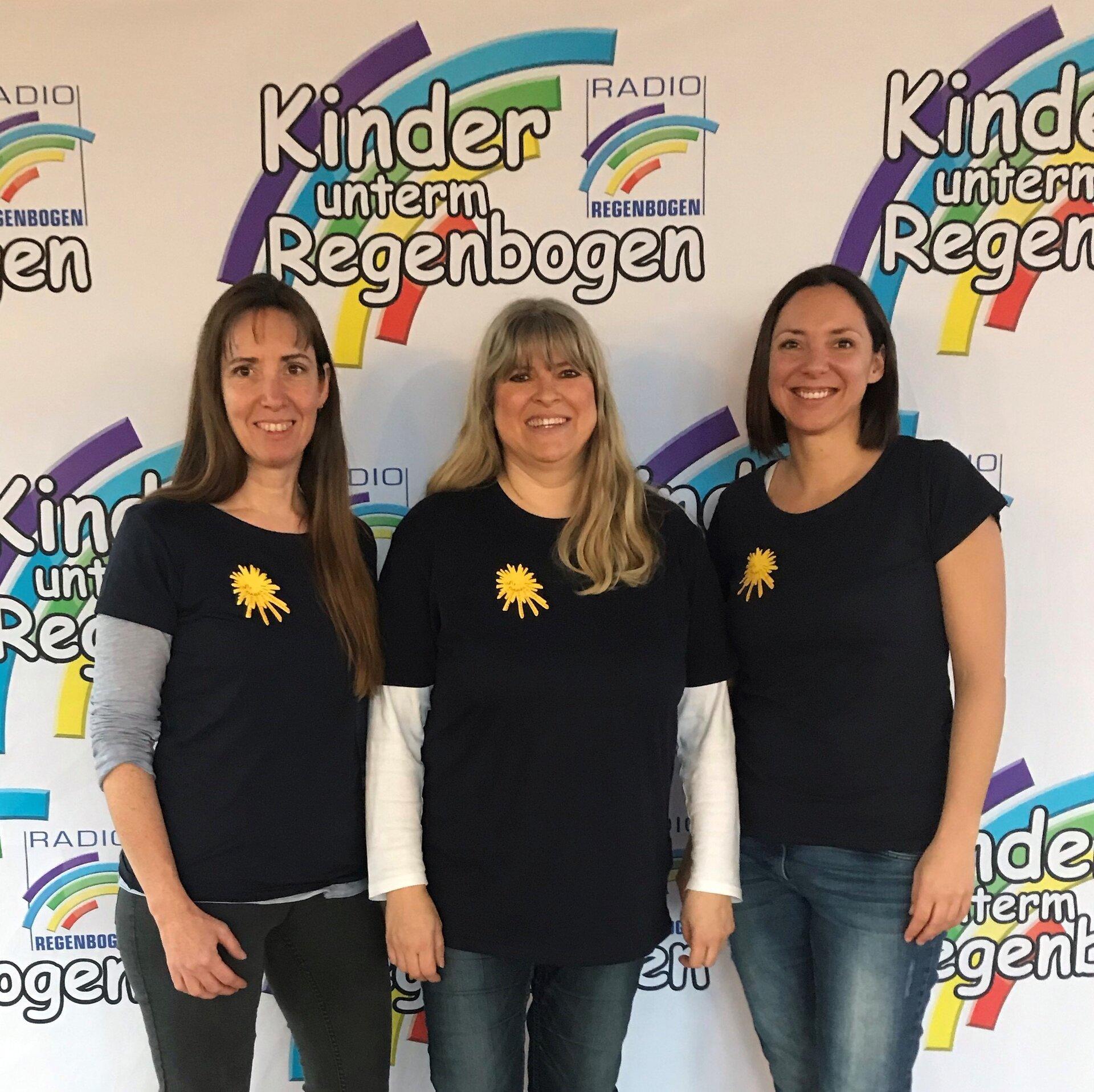 Auf dem Bild sieht man Heike Klemm, Petra Doering und Tina Luhn vor Kinder unterm Regenbogen-Logo