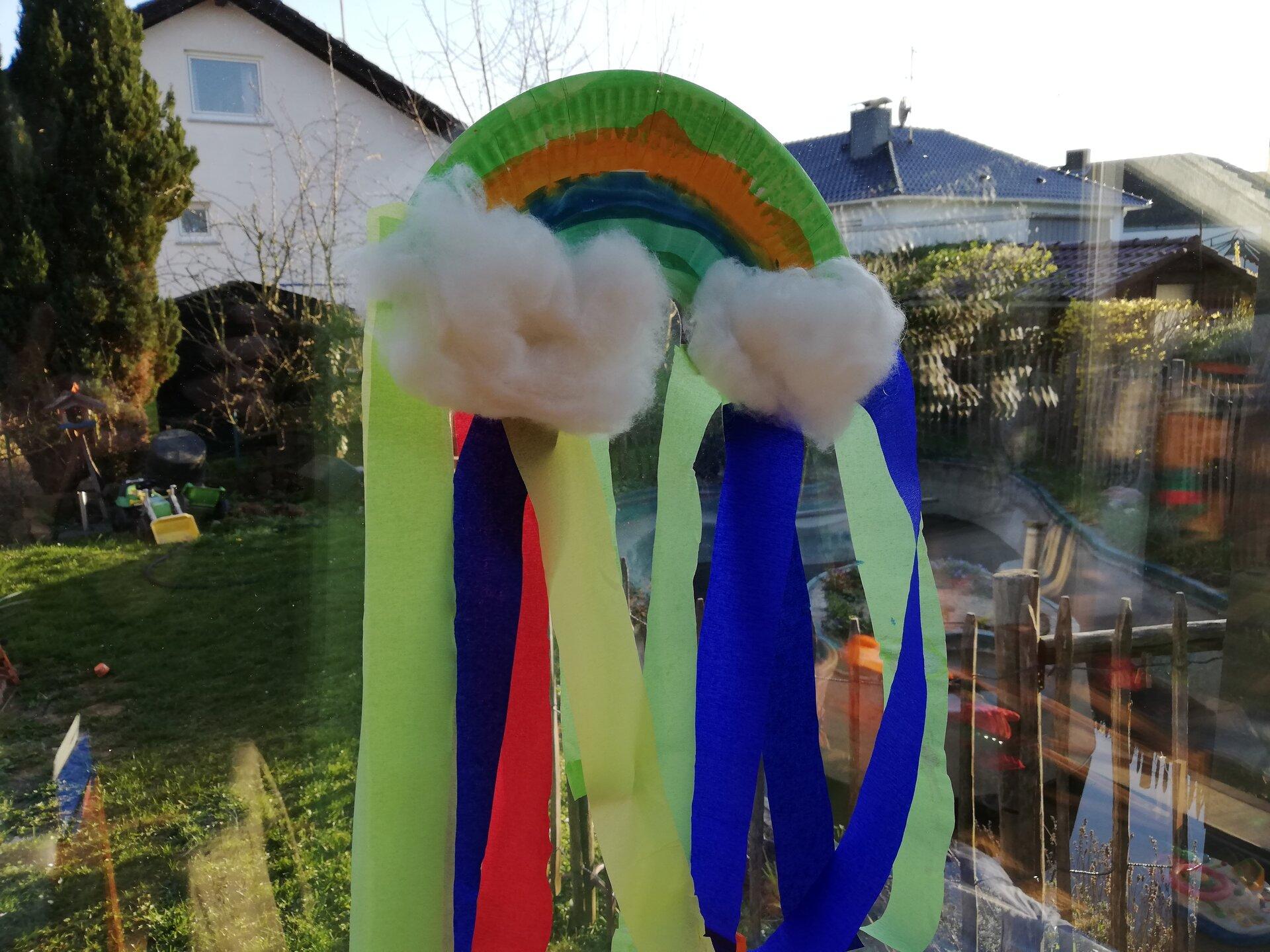 Bild zeigt einen gebastelten Regenbogen am Fenster