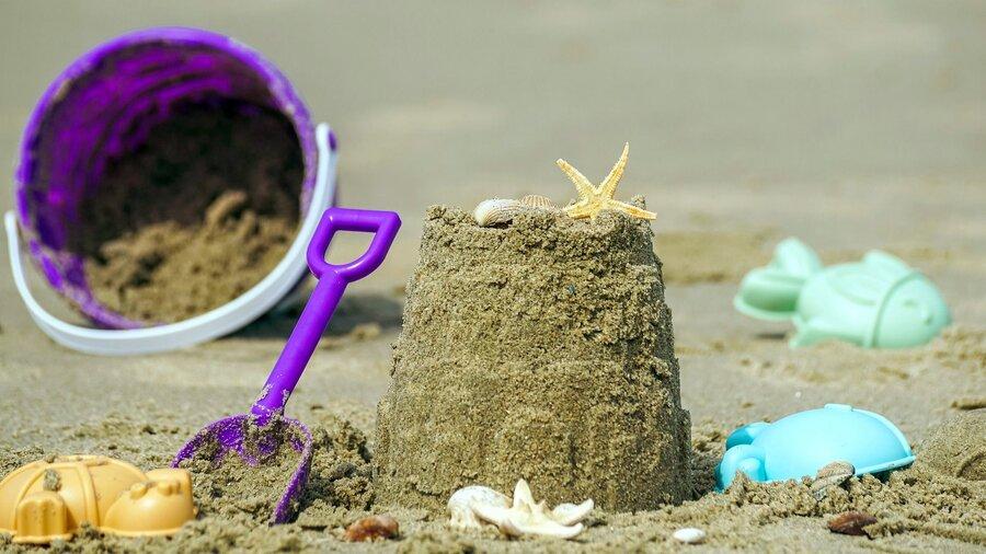 Sandspielzeug und eine Sandburg am Strand