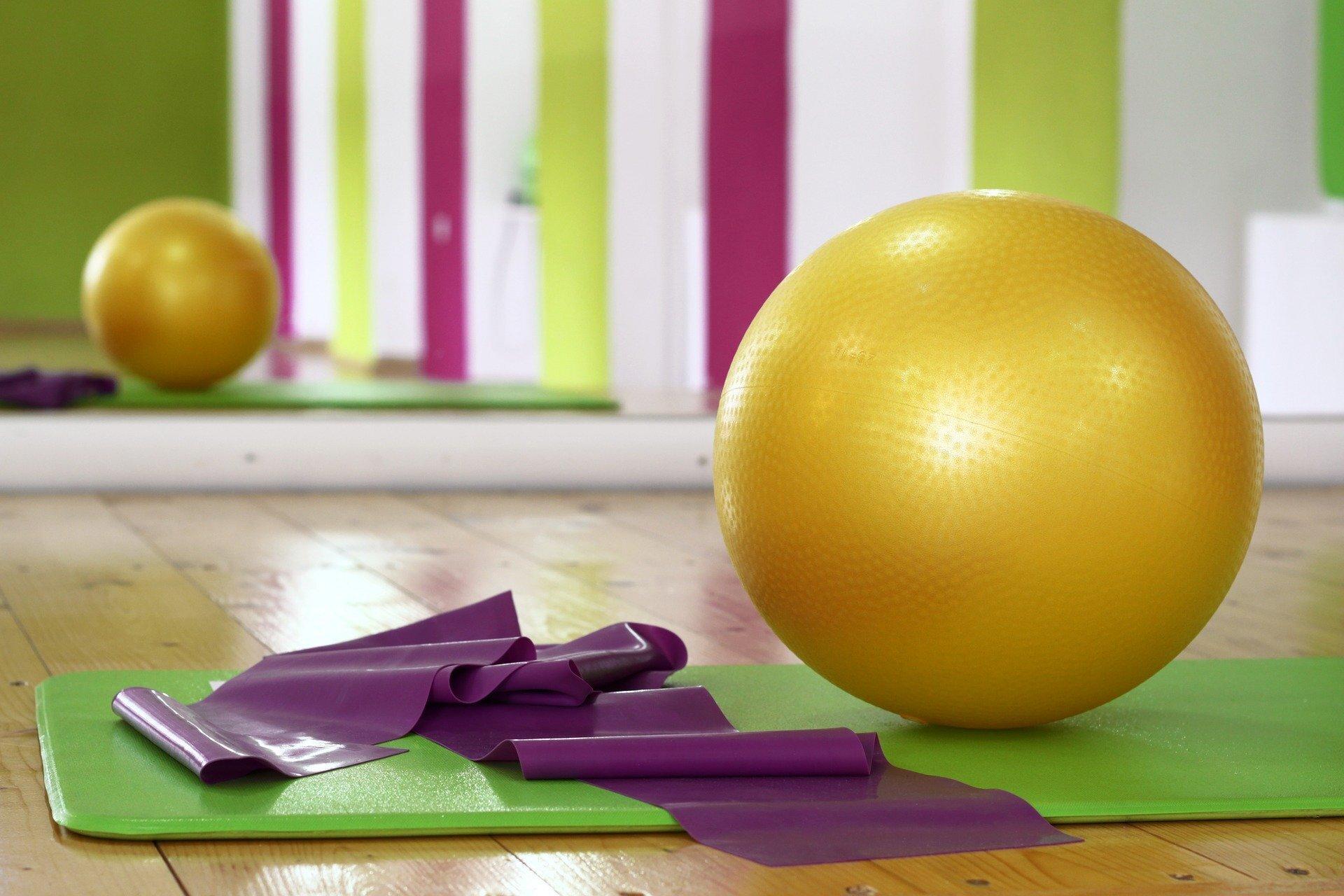 Ein Gymnastikball und ein Fitnessband auf einer Sportmatte