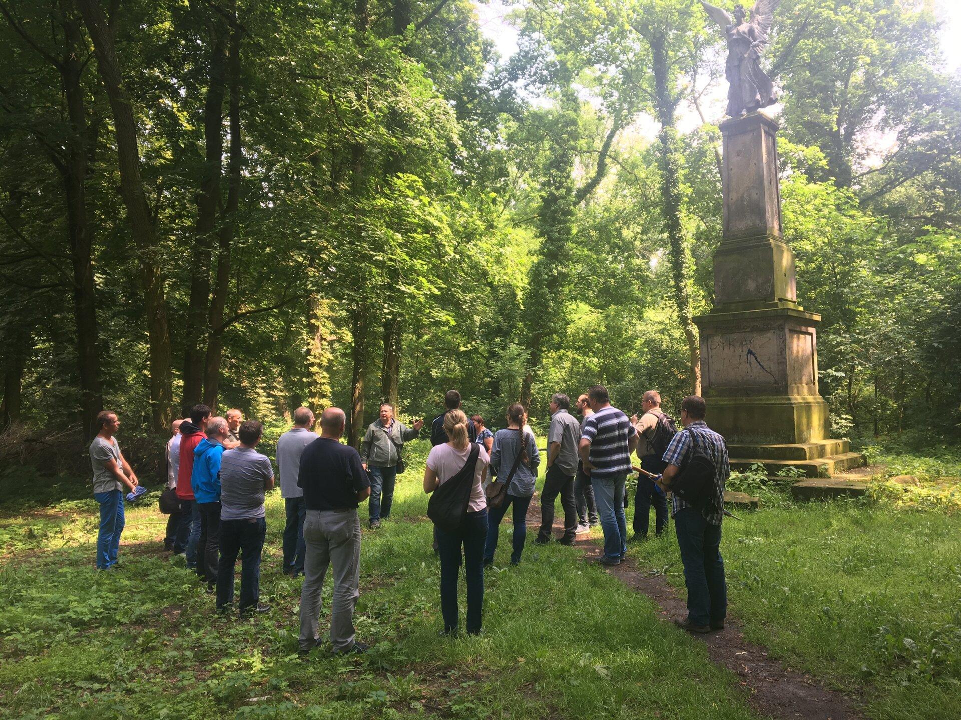 Eine Reisegruppe steht mit ihrem Gästeführer vor dem Friedrichsdenkmal im Park von Tamsel