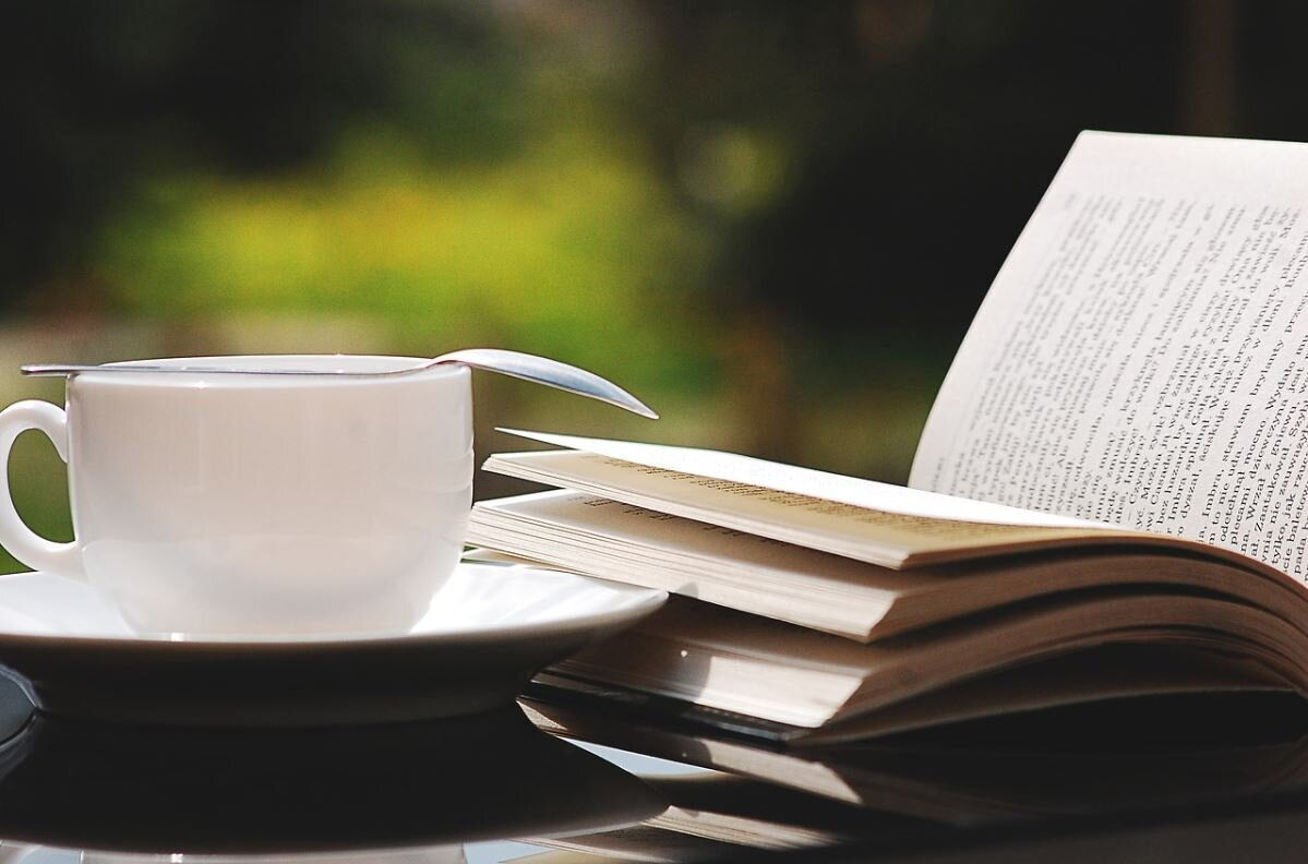 Bild zeigt ein aufgeschlagenes Buch und eine Tasse; Foto: pixabay