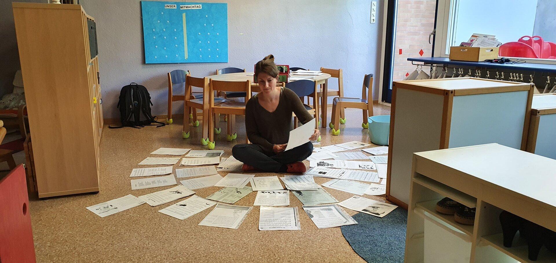Bild zeigt Erzieherin auf dem Boden sitzend mit vielen Briefen