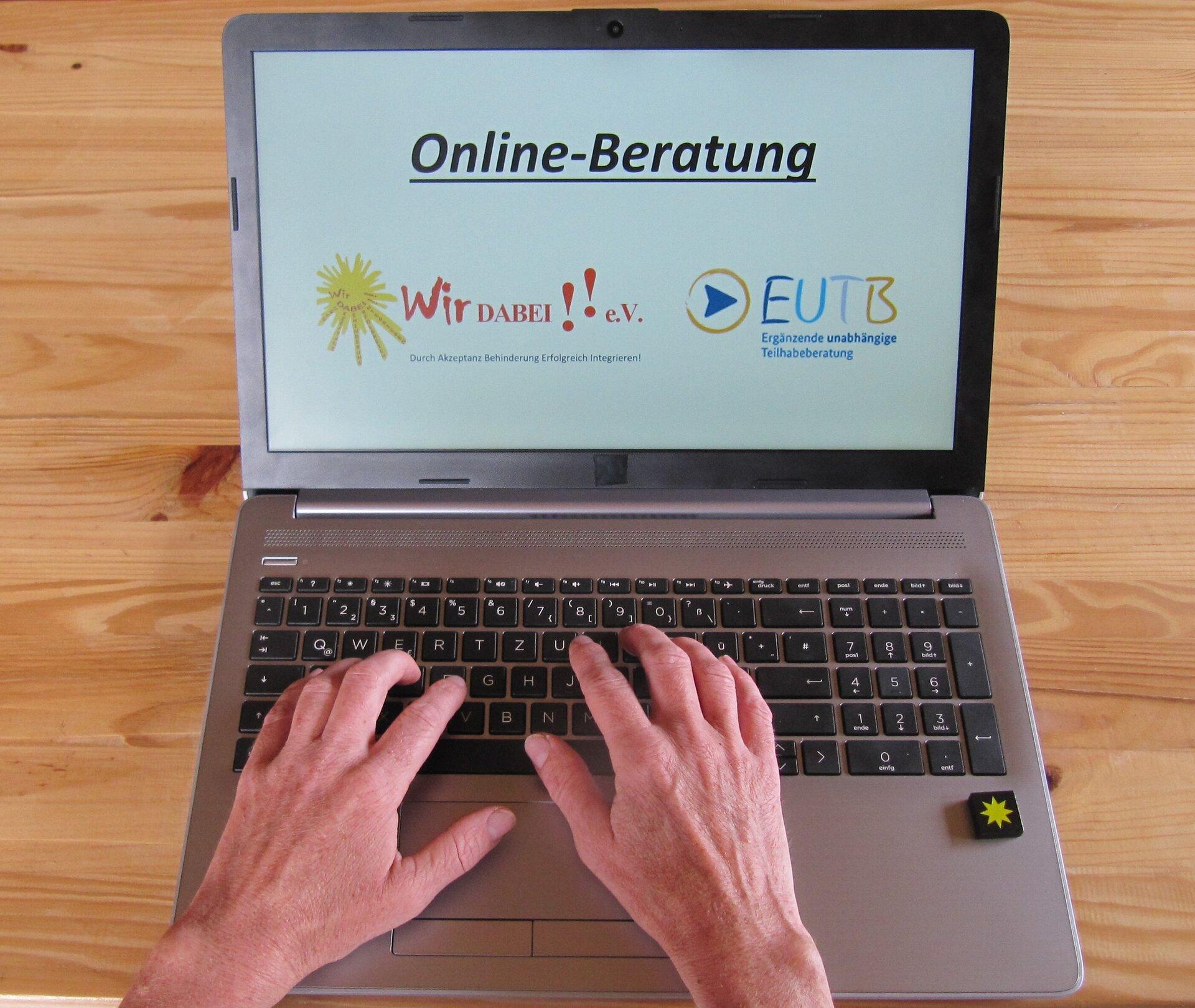 Auf dem Bild sieht man Hände, die auf Notebook schreiben. Auf dem Notebook steht Online-Beratung.