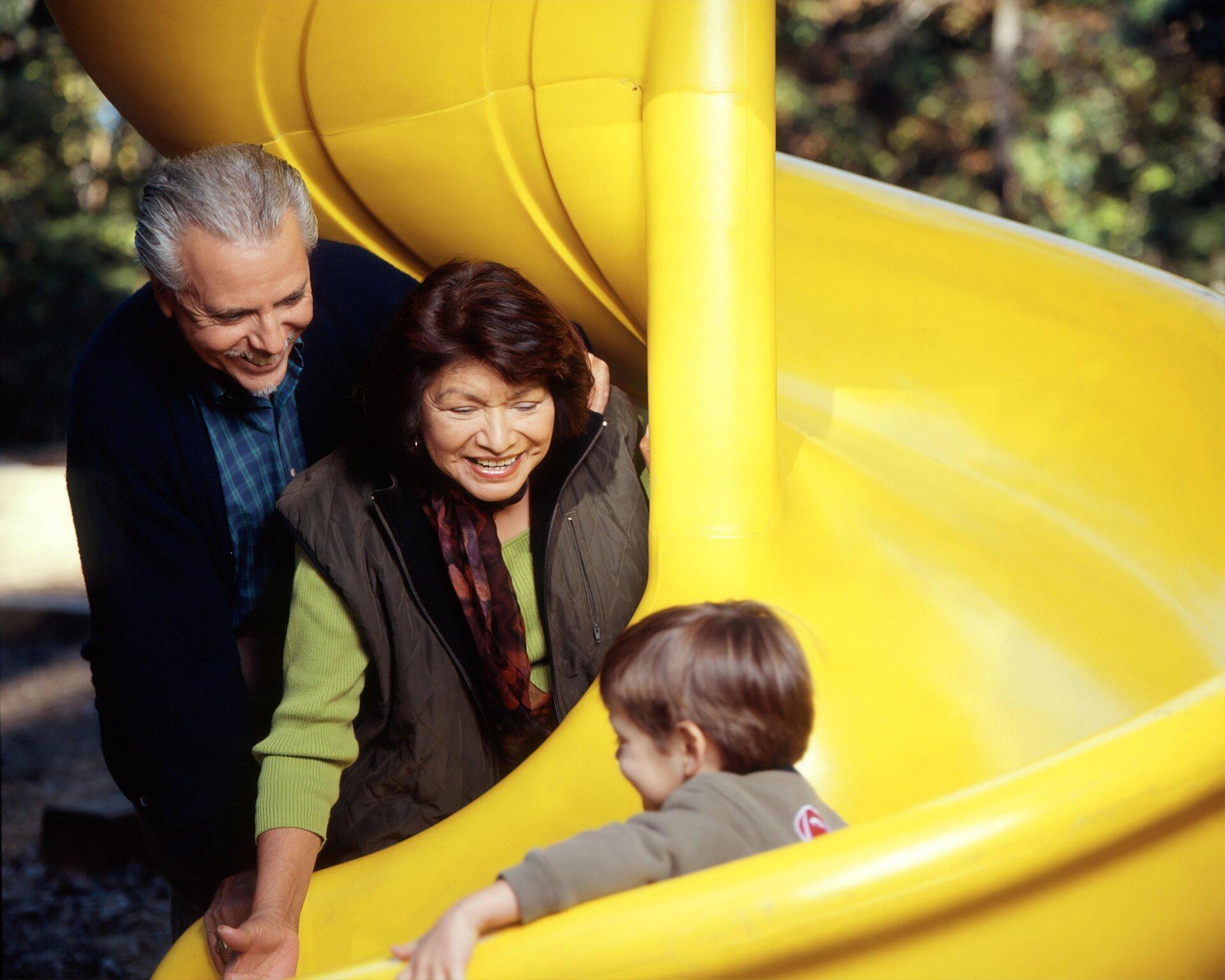 Ein älterer Mann und eine ältere Frau stehen neben einer Rutsche, auf der ein Kleinkind rutscht.