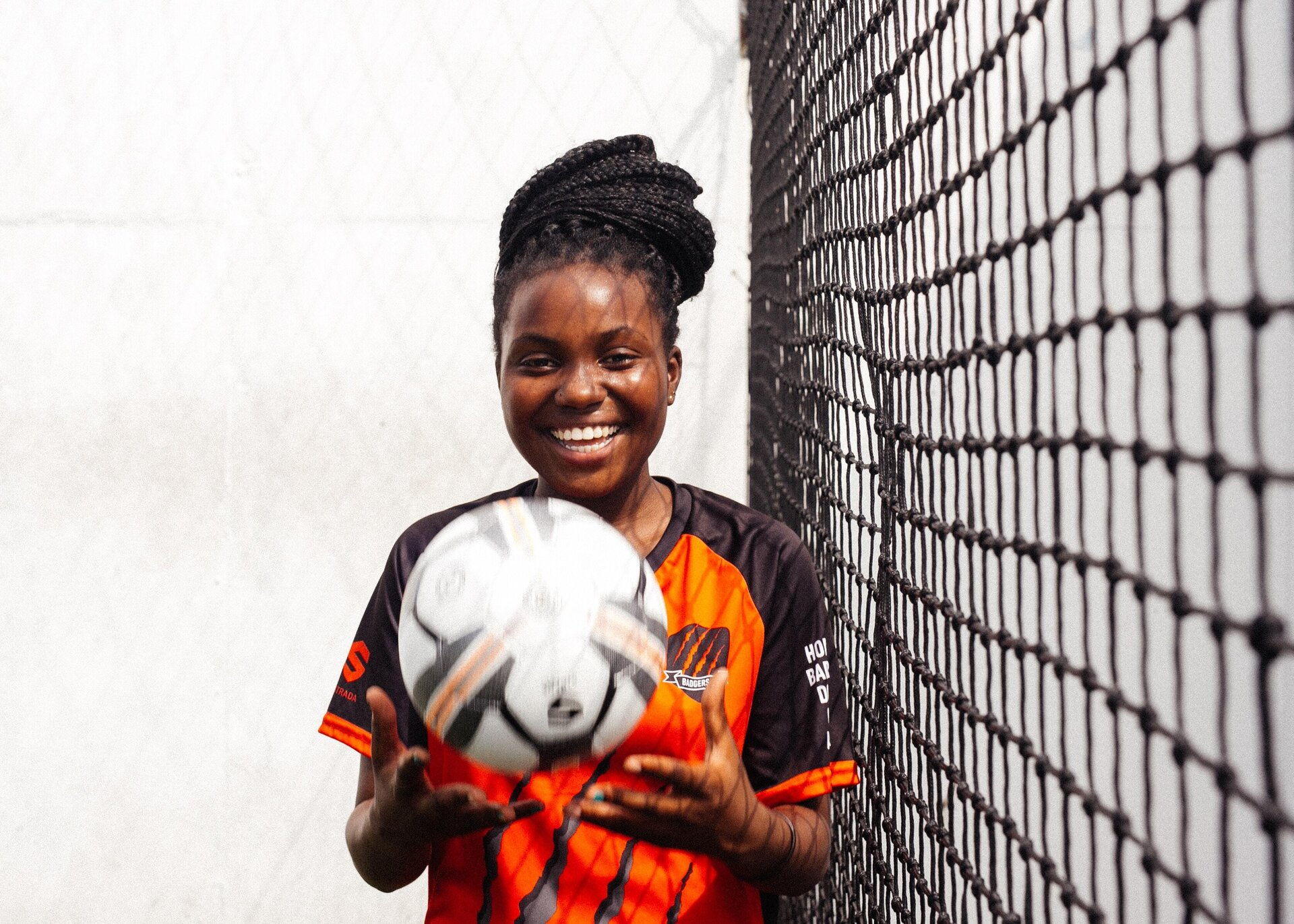 smiling-girl-in-black-and-orange-uniform-holding-soccer-ball-3886257