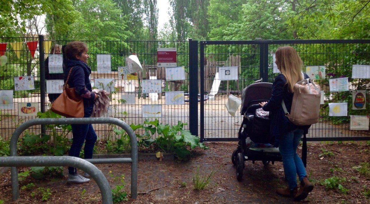 Eltern beim Betrachten der Kinderbilder am Kita-Zaun