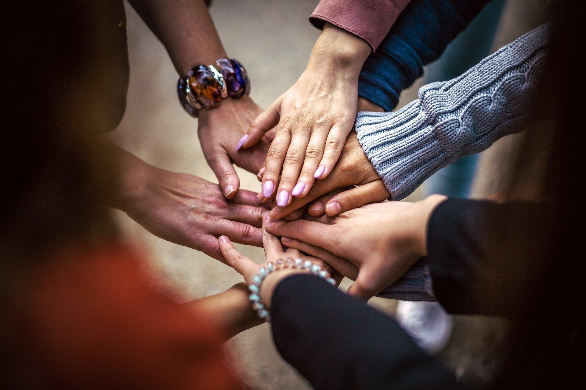 Eine Gruppe Menschen legt ihre Hände übereinander