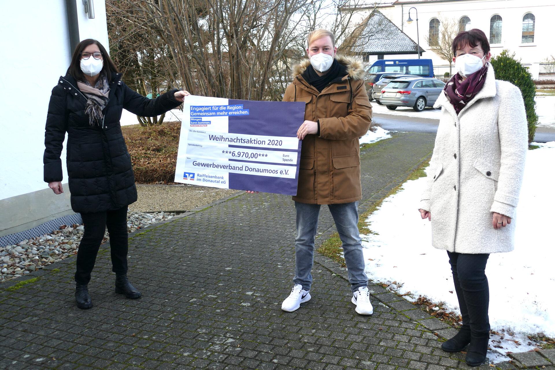 menschen mit Spendenscheck