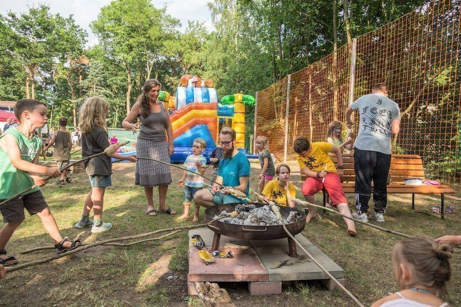 Kinder und Erwachsene beim Stockbrot
