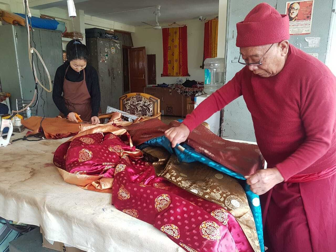 Master Tailor Phuntsok Tsering selecting the fabric - Photo by Thupten Sherap