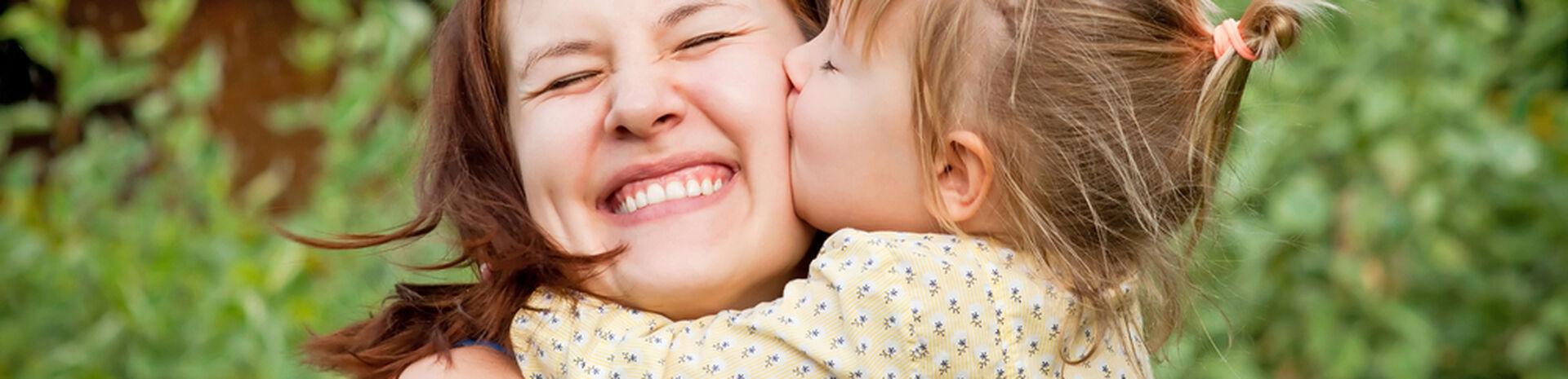 Mutter mit Kleinkind vor einer grünen Wiese