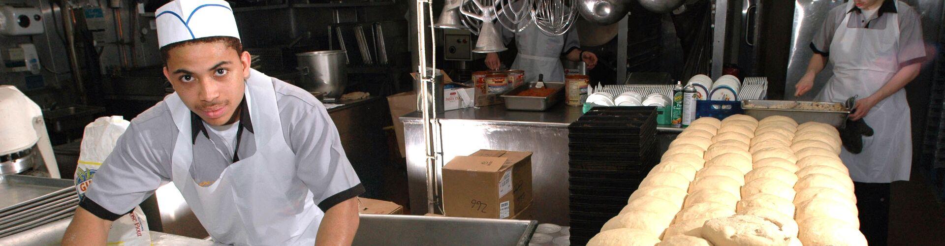 Auf diesem Bild sieht man einen Arbeitnehmer in einer Bäckerei beim Zubereiten von Broten