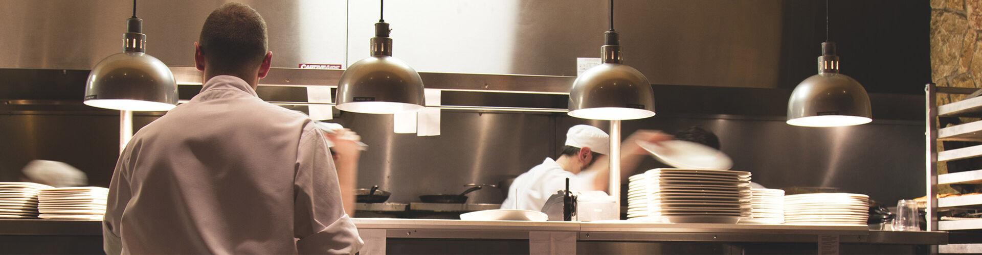 Auf diesem Bild sieht man zwei Beschäftigte in einer Großküche